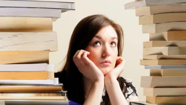 student surrounded by tall stack of books