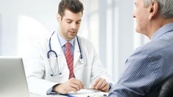 Doctor looking at chart while talking to patient