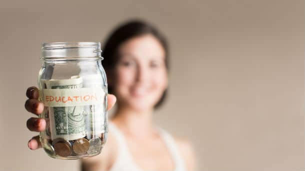 Woman holding up jar filled with money saved for education